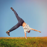 Somersault on the Grass. Toned photo of Somersault on Grass of Teenage Boy Royalty Free Stock Photo
