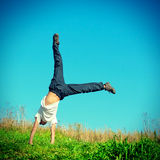 Somersault on the Grass. Toned photo of Somersault on Grass of Teenage Boy Stock Photo