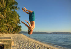 Athletic Man doing a somersault on a beach. A guy jumping of a bricked wall doing a somersault on a beach in Boracay, Philippines Royalty Free Stock Images