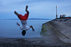 Somersault by pier. Youth makes a somersault at beach near the sea and pier at sunset time stock images