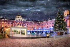 Somerset House i London med en isisbana och ett julträd Arkivbild
