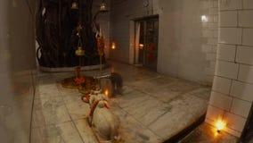 Someshwar Mahadev temple monk moves fire near entrance shivlinga trident bells statue of bull Nandi big banyan tree garlands of fl
