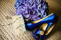 Something borrowed something Blue. Brides bouquet, garter, earrings, engagement ring and shoes waiting to be put on for her wedding day royalty free stock photos