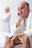 When something is bothering him. Older men supports the head by hand while sitting on the bed when his wife looks at him from behind Stock Photos
