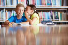 Something curious. Portrait of cute schoolgirl whispering something to her classmate in library stock photo