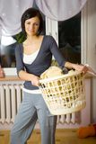 Something else to the drying?. Young woman standing in room with full laundry basket. Looking at camera. Front view Royalty Free Stock Image