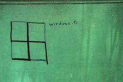 Painted and altered swastika as a window on a green background. Something forbidden to show, shown with a sense of humor Royalty Free Stock Images
