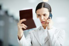 Something is going wrong. Nervous businesswoman looking at her passport and flight ticket while talking by smartphone in airport Stock Images