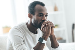 Something on his mind. Handsome young African man holding hands together and thinking while sitting on the sofa at home Stock Photography