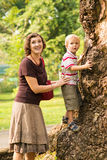 Something interesting!. Vertical image of a mother taking care of his son being on the tree in the zoo royalty free stock images