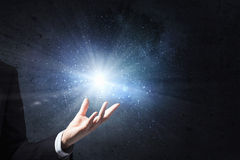 Something magic. Close up of male hand and light glowing in his palm Stock Photo