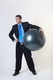 Something new in the office. Business man holding a gym ball Stock Images