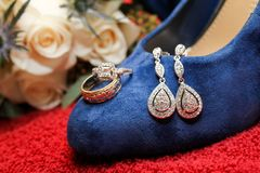 Something Old, Something New, Something Borrowed, Something Blue. Brides chosen earrings, engagement ring, wedding ban, shoes and bouquet as her wedding inches stock photography