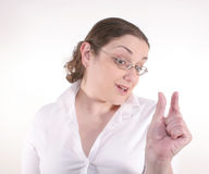 Something Small. A young brunette with glasses wearing a white button-down talking about something small (with room for object Stock Image