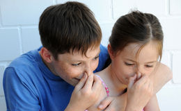 Something stinks. Siblings pinches their noses stock photos