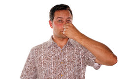 Something stinky. Man plugging nose after smelling something with a foul odor Stock Image