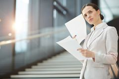 Something strange. Scowling businesswoman with financial documents expressing misunderstanding of some points Stock Photo