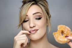 Something tasty. Beauty portrait of young woman eating a sugar ring doughnut with sugar around her mouth and lips Royalty Free Stock Image