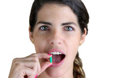 Something to ease the pain. Young Woman taking a green pill Stock Images