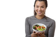 Something to eat after the work out. Happy fitness female model showing you a blow of fresh salad royalty free stock images