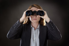 Something to find. Business woman looking through binoculars shot in the studio on gray background Stock Images