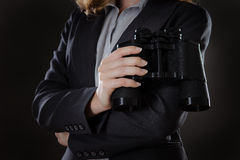 Something to find. Close up shot of business woman holding binoculars shot in the studio on gray background Royalty Free Stock Images