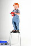 Something to fix. Cute toddlerboy standing on a chair with a toy power drill ready to fix something Royalty Free Stock Photos