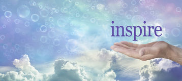 Something to Inspire You. Mans open hand with the word inspire floating above against a wide multicolored sky background, and various cloud formations and Stock Image