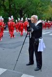 Something to Remember. Man taping, while members from the Sacred Heart University Pioneer Marching Band are making their way on Fifth Avenue during the 68th Royalty Free Stock Images