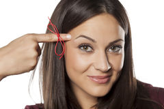Something to remind me. Forgetful young woman with a finger tied with a red thread Royalty Free Stock Images