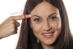 Something to remind me. Forgetful young woman with a finger tied with a red thread stock images