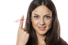 Something to remind me. Forgetful young woman showing her finger tied with a red thread stock images