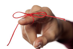 Something to remind me. Index finger tied with a red thread Royalty Free Stock Photography