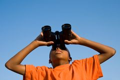 Something to see. A boy looks skywards through binoculars Royalty Free Stock Photos