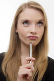Something to think about. Happy woman holding a pen deep in thought royalty free stock photography