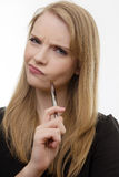 Something to think about. Happy woman holding a pen deep in thought Stock Photography