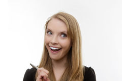 Something to think about. Happy woman holding a pen deep in thought stock images