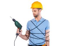 Something wrong with this drill. Frustrated young male carpenter trapped in wire holding drill and looking at it while standing against white background Stock Photos