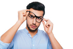 Something wrong with these eyeglasses. Frustrated young Indian man adjusting his eyeglasses while standing against white background Royalty Free Stock Image