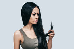 Something is wrong with my hair. Attractive young woman in casual wear looking at her long hair with serious face while standing against grey background Stock Photo