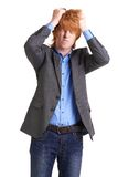 Something wrong. Portrait of young guy in smart clothes holding his head in isolation Stock Photos