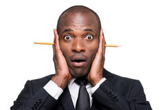 Something wrong... Surprised young African man in formalwear holding head in hands with pencil sticking out of it while standing isolated on white background Royalty Free Stock Photography
