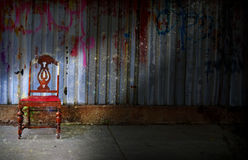 Sometime being alone is magical. Red wooden card in front of graffiti sprayed iron wall, light beam with magical sparkles emphasizing chair. Symbolizes being stock photo