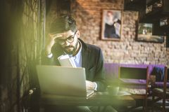 Sometimes business are not working like you want. Young businessman working on his laptop royalty free stock image