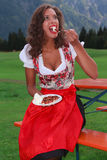 Sometimes it does not take much to be happy. Young girl in traditional Bavarian costume eating a cake Stock Photo