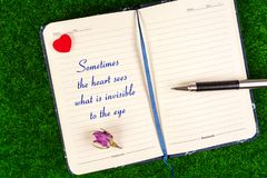 Sometimes the heart sees what is invisible to the eye. Text in notebook with heart,pen and dried rose on grass stock images