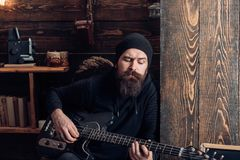 Sometimes music is all you need. Bearded man play the guitar. Rock guitarist playing music. Rock style man. Rock and. Roll music performer. Electric guitar royalty free stock photo