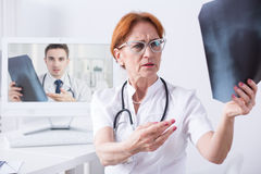 Sometimes other expert's help is necessary. Shot of a concerned doctor holding an X-ray and having a video conversation with another professional Stock Photo