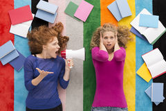 Sometimes students life is very hard. Top view of a young women shouting using megaphone and her stressed friend, colorful background Stock Image