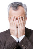 Sometimes there are situations that are out of control. Frustrated mature man covering his face by hands while standing against white background Royalty Free Stock Photography
